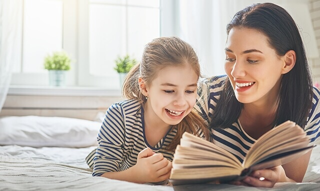 Mom reading to her daughter in bed