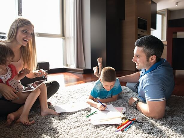 Family playing games on carpet inside